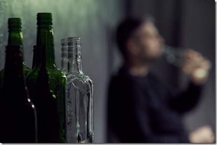 Empty bottles of alcohol with drinking man